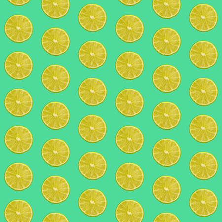 Seamless pattern of fresh green lime round cut wedges on vivid teal background Stok Fotoğraf