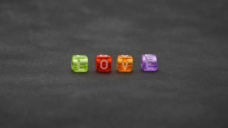 Close up word LOVE of colorful multicolor cube shape plastic beads over black background, low angle view, selective focus