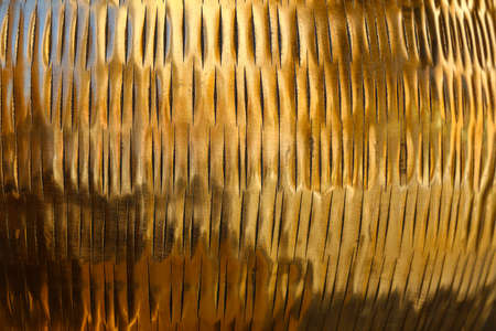 Close up background texture of shiny golden metal surface with chiseled embossing