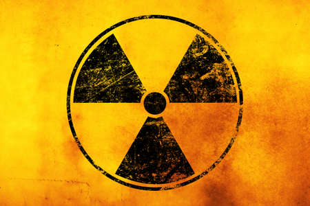 Black radioactive hazard warning sign painted over grunge yellow background with copy space