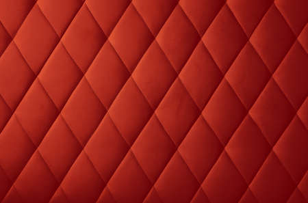 Background texture of maroon red genuine leather soft tufted furniture or wall panel upholstery with deep diamond pattern, close up