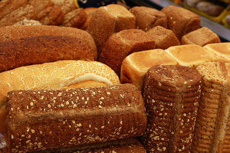 Close up selection of assorted fresh bread loaves on retail display of bakery store, high angle view Stockfoto