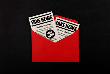 Close up brown paper mail envelope with FAKE NEWS newspapers over black background with copy space, elevated top view, directly above Stock Photo
