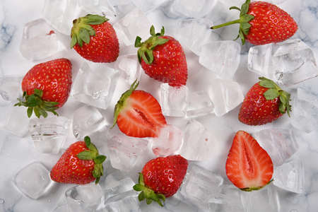 Close up fresh red ripe strawberries and ice cubes on table, el;evated high angle view, directly above