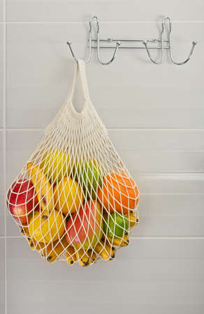 Close up assorted fresh fruits in reusable string mesh shopping bag hanging on the hook over grey wall, low angle side view Archivio Fotografico