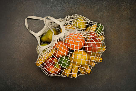 Close up assorted fresh fruits in reusable string mesh shopping bag on the floor or table, elevated top view, directly above