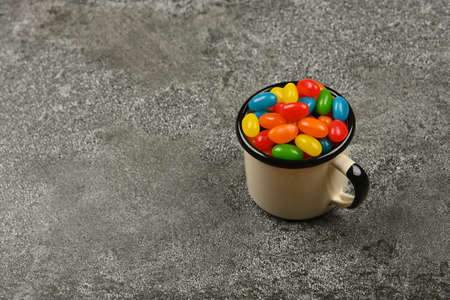 Close up multicolor jelly beans candies in vintage white metal mug on grunge gray table surface, high angle view Foto de archivo