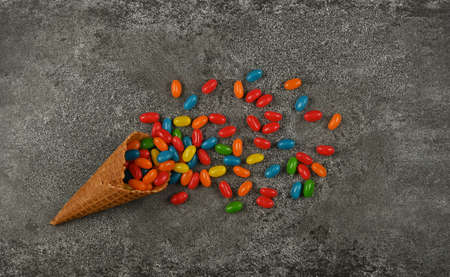 Close up multicolor jelly beans candies spilling out of in wafer ice cream cone on grunge gray table surface, elevated top view, directly above