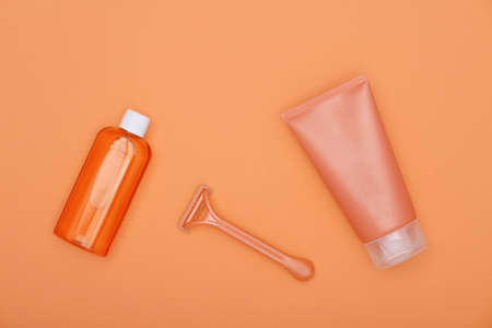 Close up feminine beauty care flat lay of shaving set on orange background, elevated top view, directly above