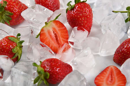 Close up fresh red ripe strawberries and ice cubes on table, high angle view