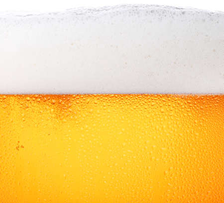 Close up background texture of pouring lager beer with bubbles and froth in frosty glass with drops, low angle side view