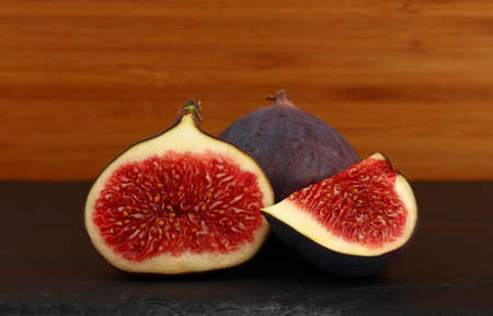 Close up one whole fresh ripe fig fruit with cut half and quarter slice on cutting board on table, low angle side view 免版税图像
