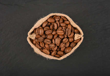 Close up one jute canvas bag of roasted Arabica coffee beans over black slate background, elevated top view, directly above
