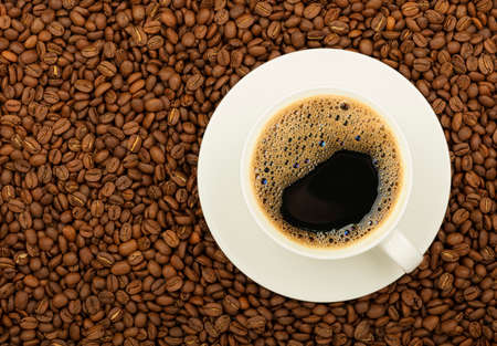Close up white cup on saucer full of black coffee over background of roasted coffee beans, elevated top view, directly above Stok Fotoğraf