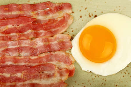 Close up English breakfast, sunny side egg and roasted bacon slices on blue plate, elevated top view, directly above Stok Fotoğraf