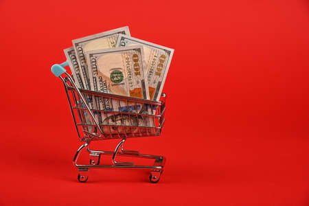 Close up several one hundred US dollar paper currency banknotes in small shopping cart over red background, low angle side view Stok Fotoğraf