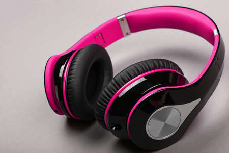 Close up modern wireless plastic purple pink headphones with big cushions on gray table, high angle view