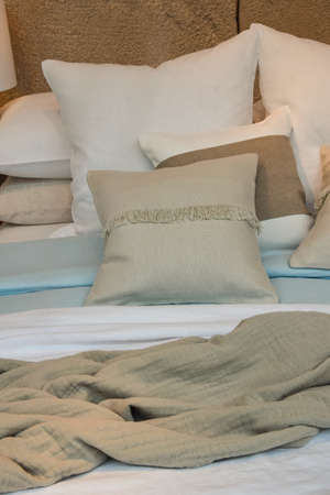 Close up well made bed with pastel color pillows and bedspread, high angle view