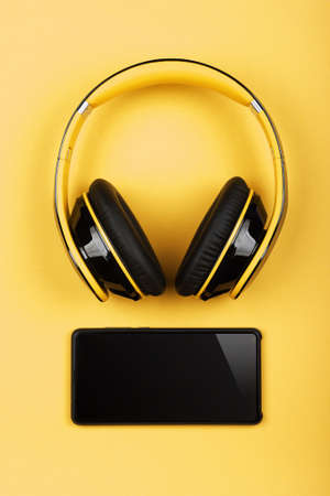 Close up modern wireless plastic yellow headphones with big cushions and black mobile phone on table, elevated top view, directly above Stok Fotoğraf