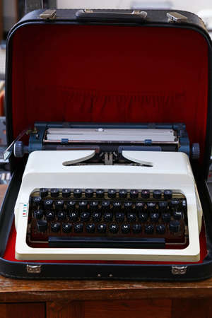 Close up one old portable desk typewriter with Latin alphabet keyboard in open leather case on table, high angle view