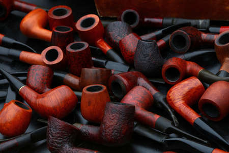 Close up many natural wooden tobacco smoking pipes on market stall, high angle view
