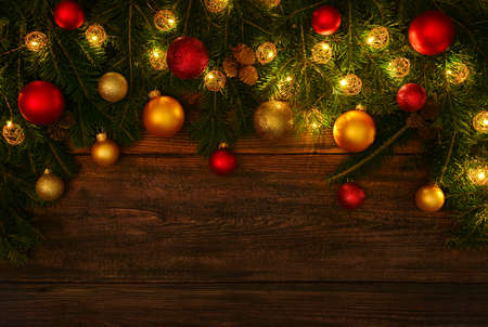 Close up fresh green spruce or pine Christmas tree branches with cones, lights, colorful balls and baubles decoration, over dark brown wooden planks background with copy space