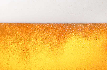 Close up background texture of pouring lager beer with bubbles and froth in frosty glass with drops, low angle side view Stock fotó