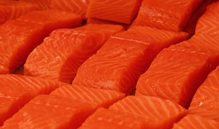 Close up several fresh raw salmon fish filet steaks on ice at retail display of fisherman market, high angle view Stock fotó