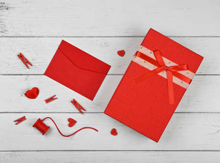 Preparing Valentine gifts, red box, hearts, twine, clothespins and note in paper envelope on white wooden table background, close up flat lay, elevated top view, directly above