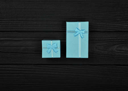 Valentine template of two closed small blue gift boxes with ribbon bows over black wooden table background, close up flat lay, elevated top view, directly above