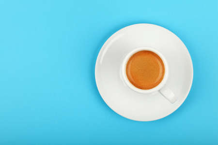 Close up one white cup full of espresso coffee on saucer over blue background, elevated top view, directly above Stock fotó