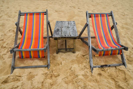Two empty colorful canvas lounge sling chairs and wooden table on sand beach of resort in Thailand, front view, high angle