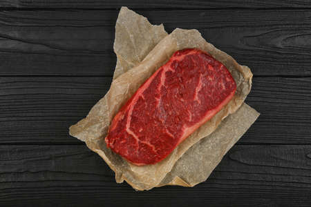Close up one aged prime marbled raw sirloin beef steak on brown paper parchment wrapping over black wooden table background, elevated top view, directly above