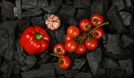 Close up raw red bell pepper on black lump charcoal pieces ready for barbecue grill cooking, elevated top view, directly above Stok Fotoğraf