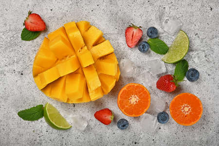 Close up preparing fresh ripe cut mango and mixed fruits dessert on gray stone cutting board, elevated top view, directly above