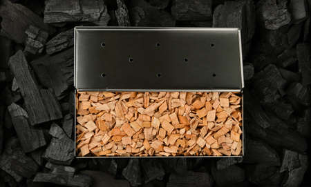 Close up one stainless steel metal smoker box with hardwood alder chips on black lump charcoal pieces, ready to barbecue grill and smoke food, elevated top view, directly above