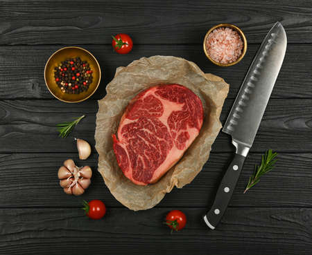 Close up one aged prime marbled raw ribeye beef steak on brown paper parchment wrapping, with knife and spices, over black wooden table background, elevated top view, directly above