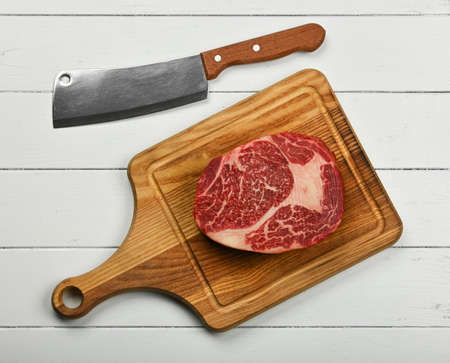 Close up one aged prime marbled raw ribeye beef steak on brown oak wood cutting board with cleaver knife, over white wooden table background, elevated top view, directly above Stok Fotoğraf