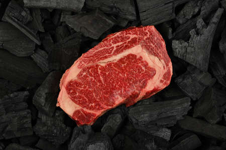 Close up one aged prime marbled raw ribeye beef steak on black lump charcoal pieces ready for barbecue grill cooking, elevated top view, directly above Stok Fotoğraf