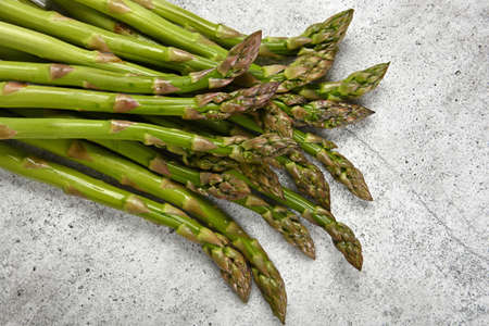 Close up bunch of fresh green asparagus on cutting board or grey stone table surface, elevated top view, directly above Stok Fotoğraf