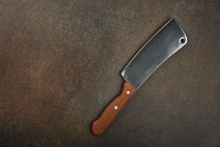 Close up one butcher metal meat cleaver with wooden handle on grunge kitchen table surface, elevated top view, directly above