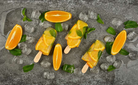 Close up three fruit ice cream with fresh orange slices, green mint leaves and ice cubes on gray table surface, elevated top view, directly above