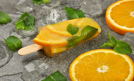 Close up one fruit ice cream with fresh orange slices, green mint leaves and ice cubes on gray table surface, high angle view