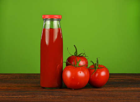 Close up one glass bottle of ketchup sauce and fresh red tomatoes on wooden table over green background with copy space, low angle view