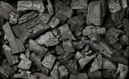 Close up background texture of many black lump charcoal pieces ready for barbecue grill, elevated top view, directly above