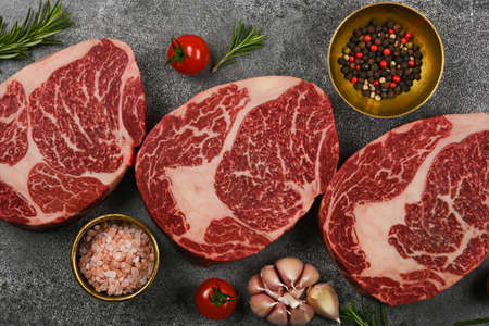 Close up three aged prime marbled raw ribeye beef steaks with spices, over stone table background, elevated top view, directly above