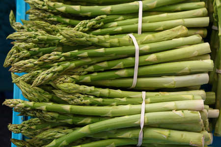 Bunch of fresh green asparagus shoots at retail market display, close up, high angle view Stok Fotoğraf