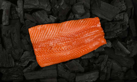 Close up raw salmon fish fillet on black lump charcoal pieces ready for barbecue grill cooking, elevated top view, directly above