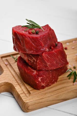 Close up three staked aged prime marbled raw tenderloin or fillet mignon beef steaks on brown oak wood cutting board, with spices, over white wooden table background, high angle view