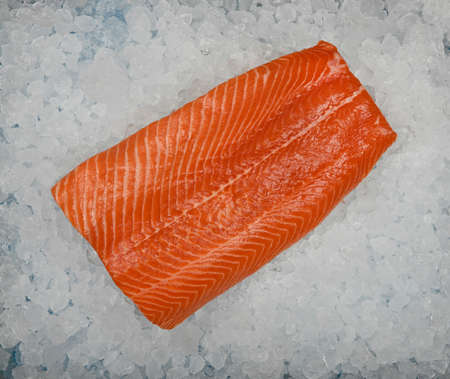 Close up one fresh raw salmon fish fillet on background of crushed ice on retail display, elevated top view, directly above